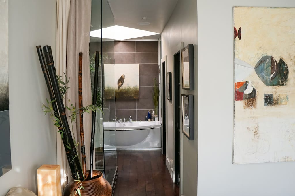 Big modern shower apart from the comfortable bath under a prominent skylight