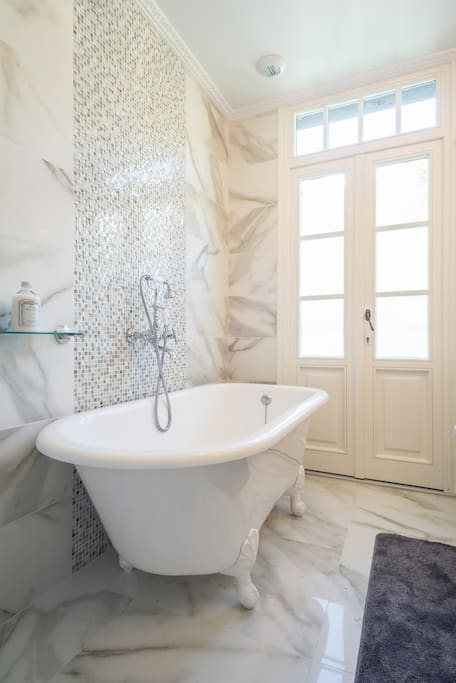 Luxury white marble main bathroom with clawfoot bath