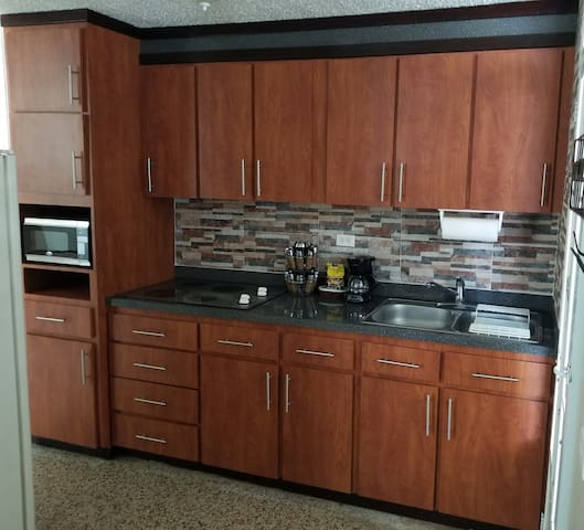 Full kitchen: coffee maker, microwave, toaster,  electric stove top, refrigerator, cooking accessories, , cutlery, glasses, and more.