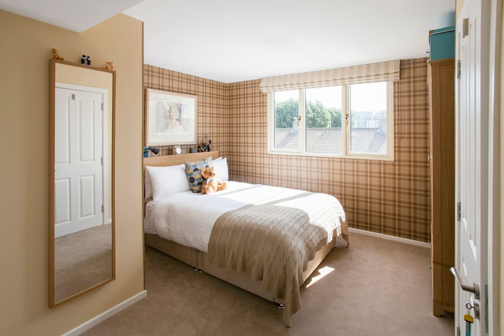 The second floor en-suite bedroom. Light floods the room from the large window which offers views of the city skyline. Double glazed and block out blinds ensure a peaceful sleep on the comfy king bed.