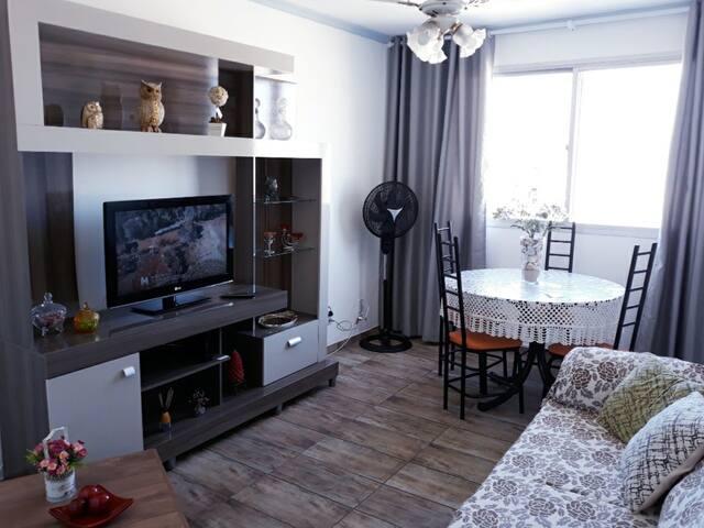 Sala confortável com sofá retrátil e TV tela plana