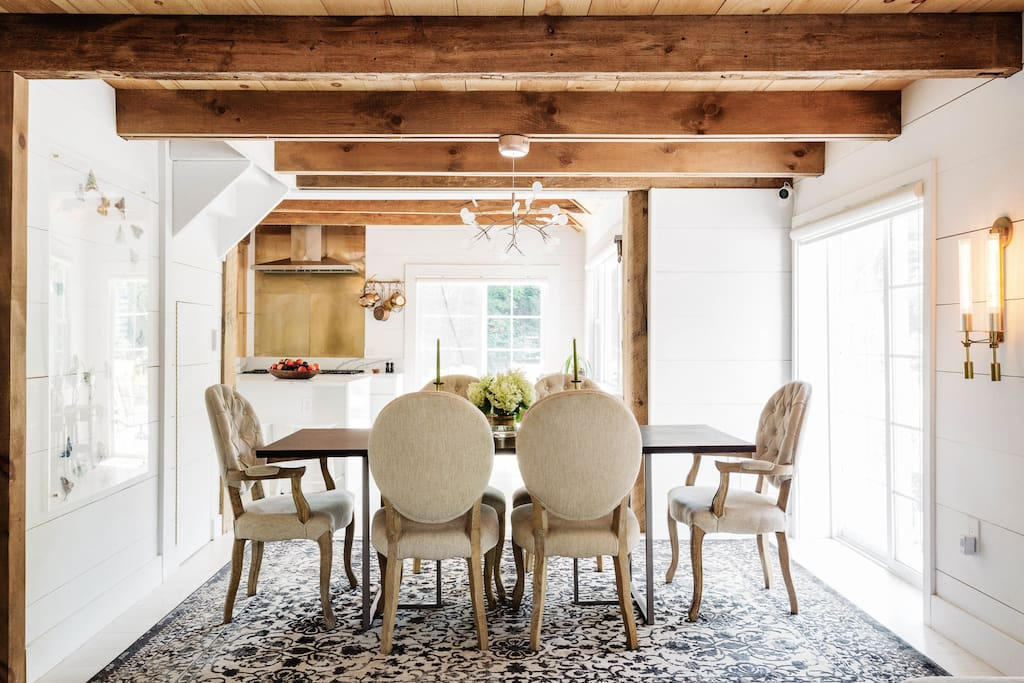 Dining Room With Reclaimed Wood Ceilings Reclaimed wood beams continue into the dining room, where they infuse the space with warmth. Tufted armchairs complement the country aesthetic while still feeling sophisticated.