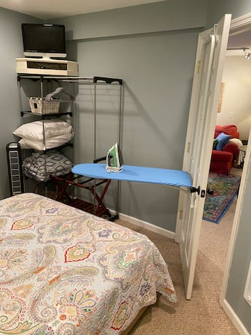 The ironing board folds up against the door to save you space! The TV is hooked up to a Roku device. Also shown is the wardrobe area with a luggage rack, hangers, and basket for your convenience, as well as extra pillows, blankets, fan, and heater.