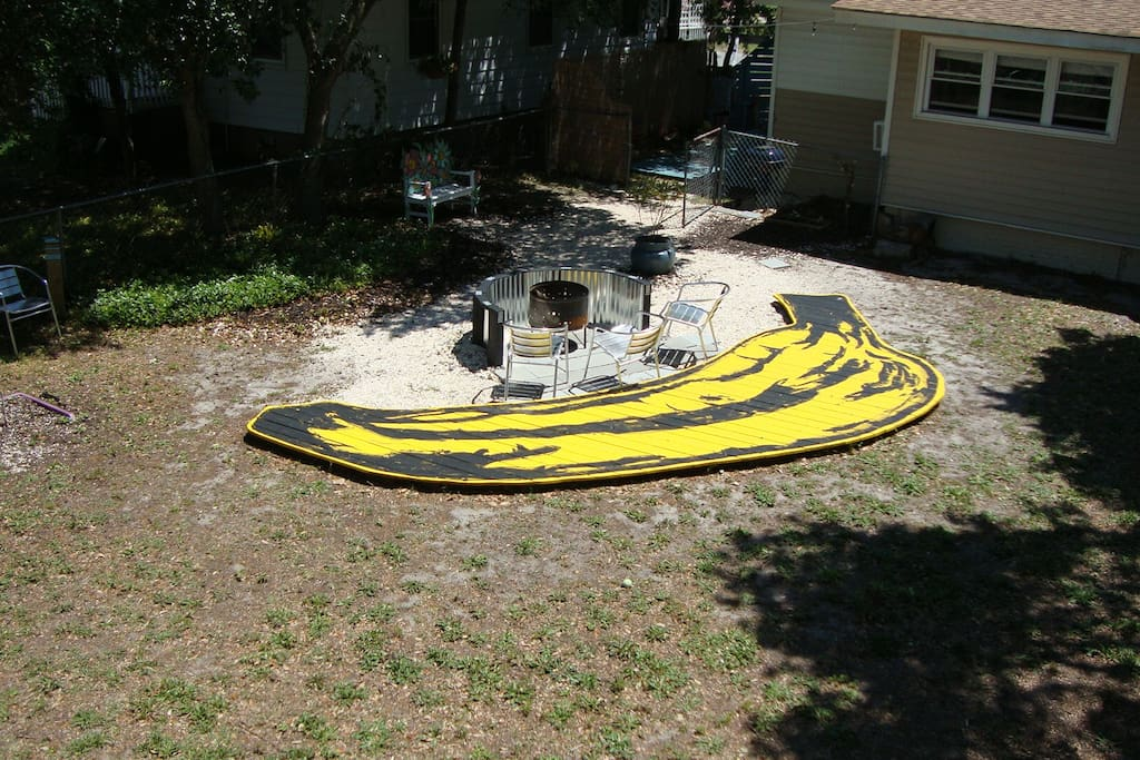 """""""The Banana!"""" A custom built deck adorns the large fenced-in backyard complete with fire pit."""