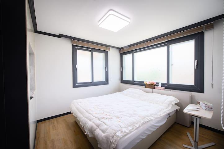 침대방. 일룸 투윈모션베드로 편안한 휴식을 준비하였습니다. 사이드 테이블이 준비되어 있습니다. 창은 해가뜨는 동쪽과 남향으로 큰창이 있으며 블라인더가 설치되어 있습니다