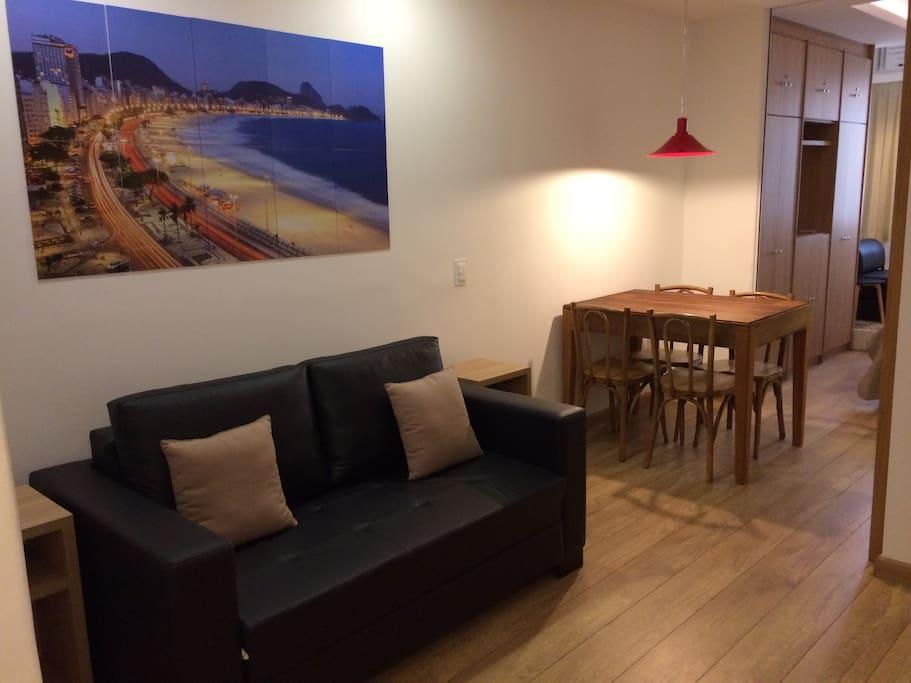 Sala de estar reversível com sofá cama e espaço de refeições.