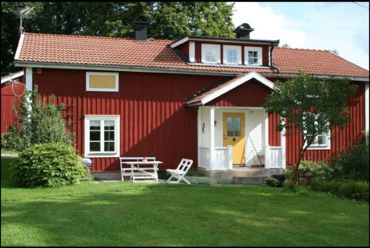 Huset sett från trädgården. Med solig uteplats  med grill.  The house seen from the garden.
