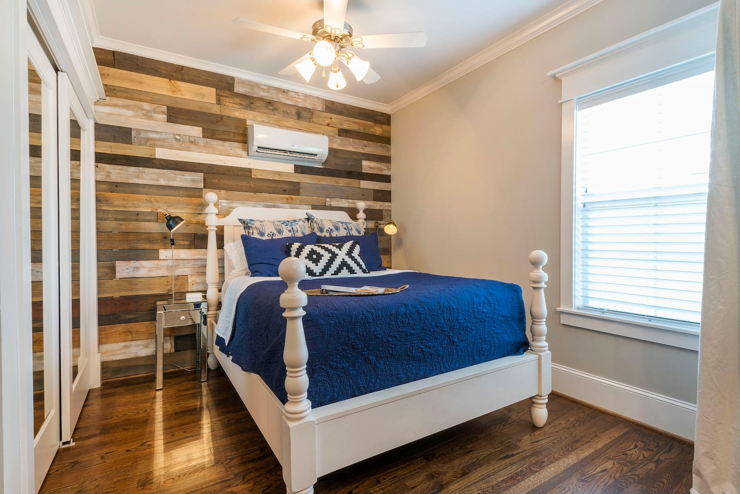Queen size pillow top mattress flanked by reading lights and charging stations all set against a reclaimed wood wall
