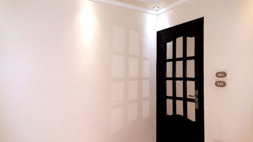 * Second Room  White Wall. * Woody Door With Mirror. * View from the inside room with a locked door.