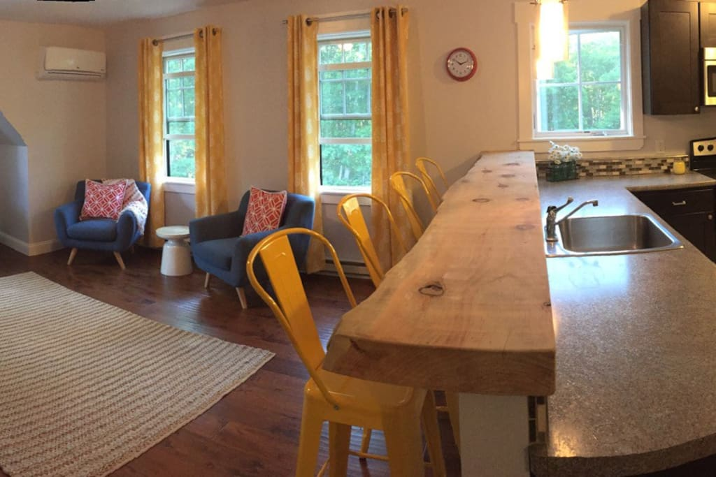 Living area, it's bright and sunny.  A/C for comfort in the warmer months.  There's a really cool custom bar top too!