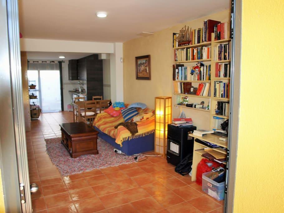 Os invitamos a compartir uno de los placeres de la casa: los libros. Al fondo, la cocina equipada.