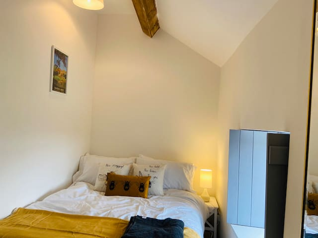 Bedroom two with a new double bed, Egyptian cotton bedding, oak beams, countryside views and wardrobe area.