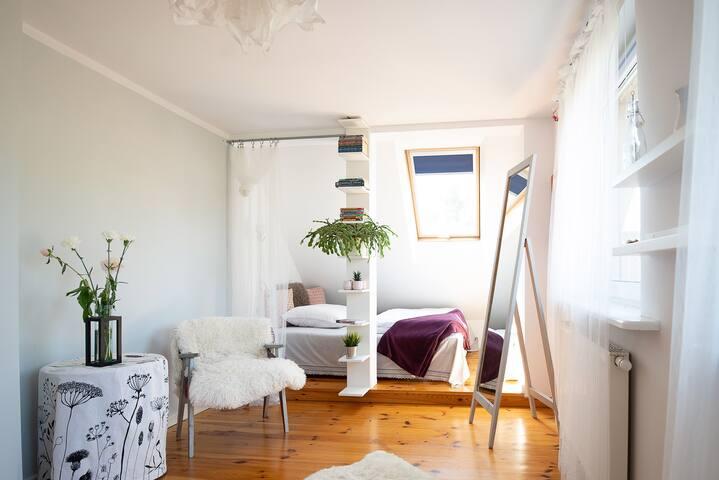 Główna sypialnia z podwójnym łóżkiem i toaletą | Main bedroom with a double bed and a half-bath