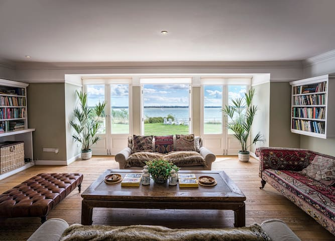 The living room is furnished with 3 sofas, a leather stool, a coffee table and a well-stocked bookshelf. The triple French doors lead out onto the terrace, offering magnificent sea views.