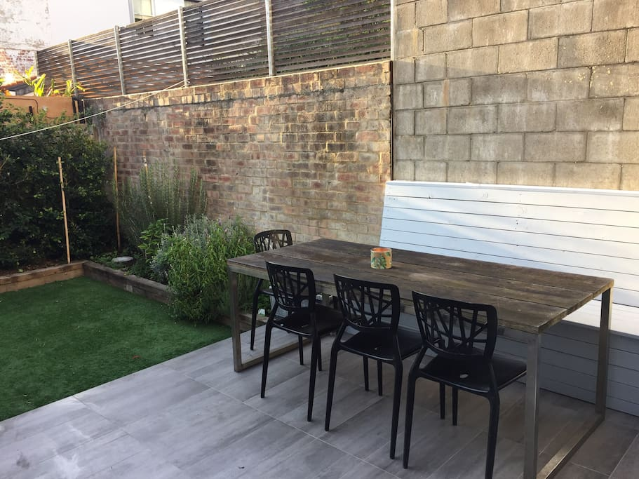 Courtyard - table seating 6 guests comfortably. This space is bathed in sunshine most of the day - lovely spot to sit & read the papers or enjoy a family lunch or dinner.   Help yourself to herbs from the herb garden