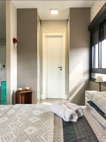 Ambiente integrado, arejado, iluminado, com cortinas persianas blackout, arcondicionado, 2 armário para roupas, sofá cama, mesa para refeições e trabalho, cozinha.