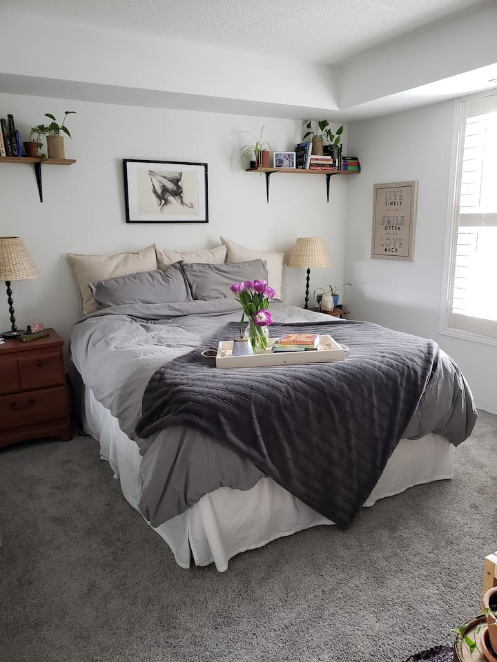 Beautiful main bedroom with lots of natural light with air purifying plants.
