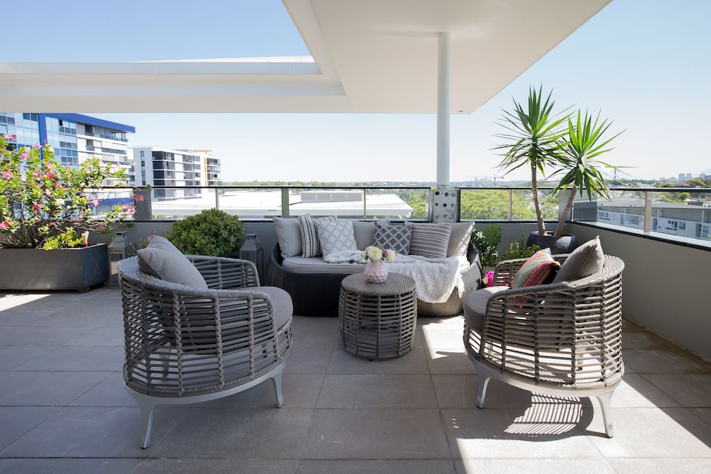 Rooftop lounge overlooking pools, gyms, historic architecture, with views of Sydney CBD and ANZAC bridge