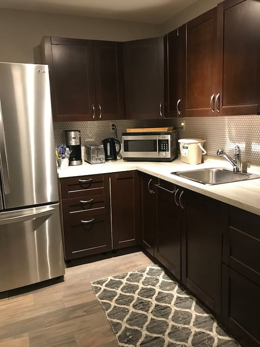 Well appointed kitchen with a full size stainless steel fridge, coffee maker, toaster oven, convection microwave, induction burner and electric frying pan toaster and all crockery.