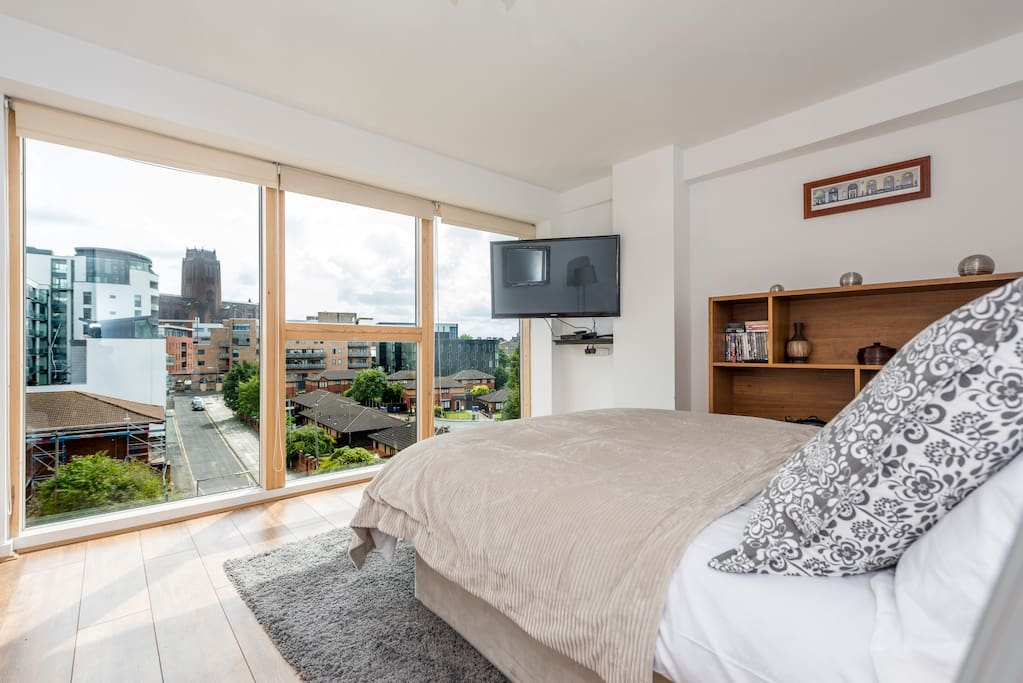 "Bedroom 1 - master bedroom with exquisite views of the Liverpool Cathedral, the fifth largest in the world! Relax in front of the wall mounted 43"" Samsung TV complete with a large selection of DVDs."