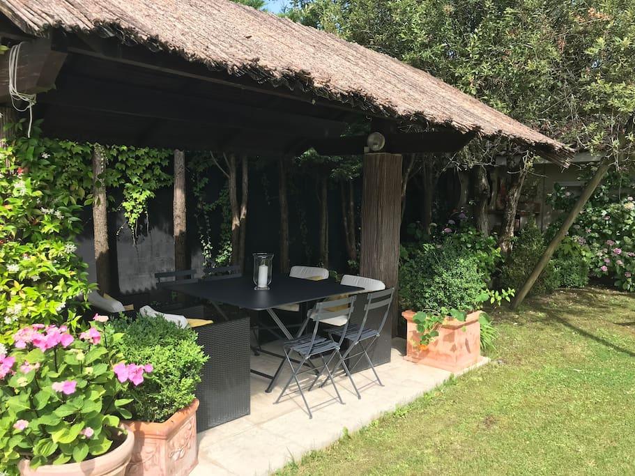Petite paillote, équipe d'un salon de jardin fermob gris, avec fauteuils et chaises coordonnées. Le coin barbecue juste à côté.. pour passer des dej et soirée conviviaux...  avec vue sur la piscine...