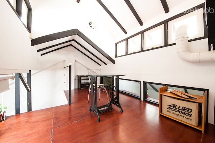 View of top of loft stairs. Loft can be R&R chillax area or bedroom. Can easily fit a King AND queen bed with ample space in between. 4 Windows on each side of jack roof.
