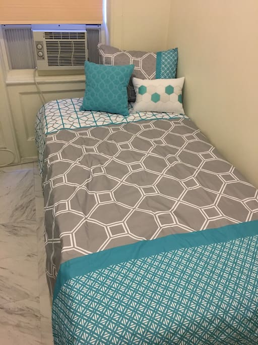 Twin size bed, pillow, decorative pillows and AC unit.
