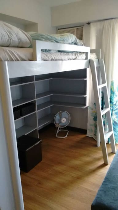 Elevated double bed with ample closet space below. Air conditioning provided.