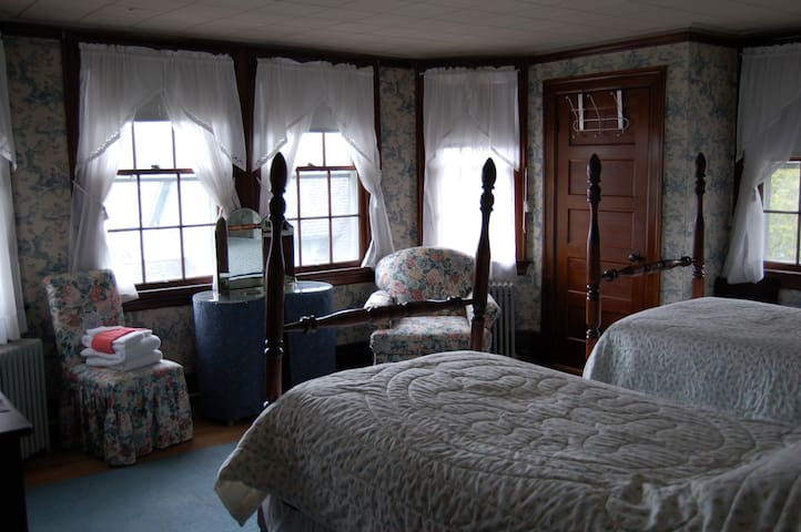 Toile room with two twin beds, dressing table and window seat