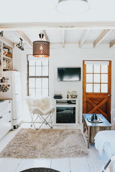 """The living/kitchen room downstairs has an electric fireplace and a smart telly. The coffee table has a pop up top for """"dining"""" and """"laptopping."""""""