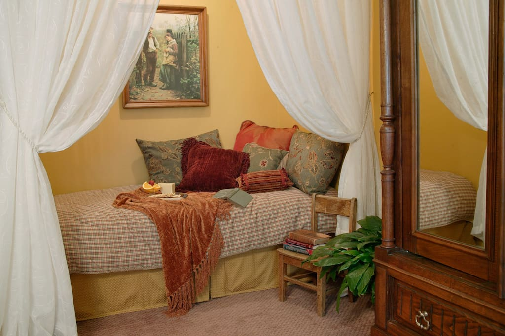 Twin bed tucked away in alcove.