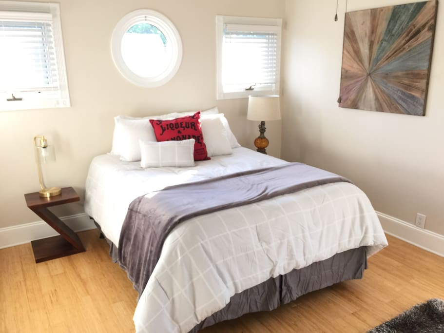The bright and airy upstairs bedroom has a ceiling fan and lots of windows.