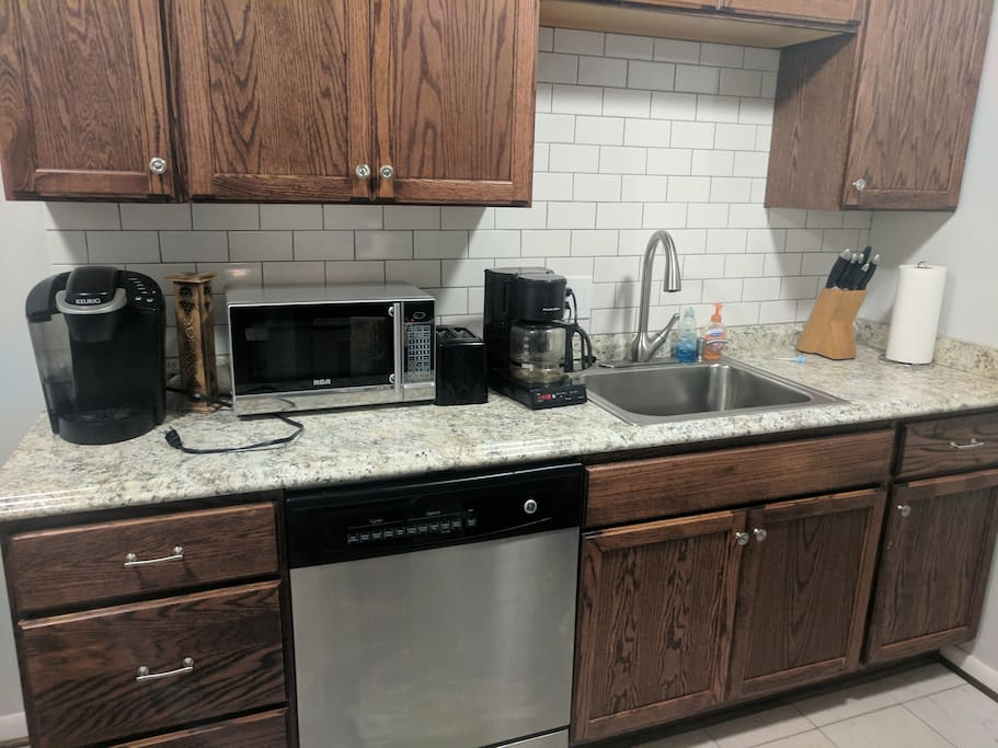 Kitchen with the basic Coffee Maker microwave oven ,Keurig coffee maker, utensils Stove and Fridge