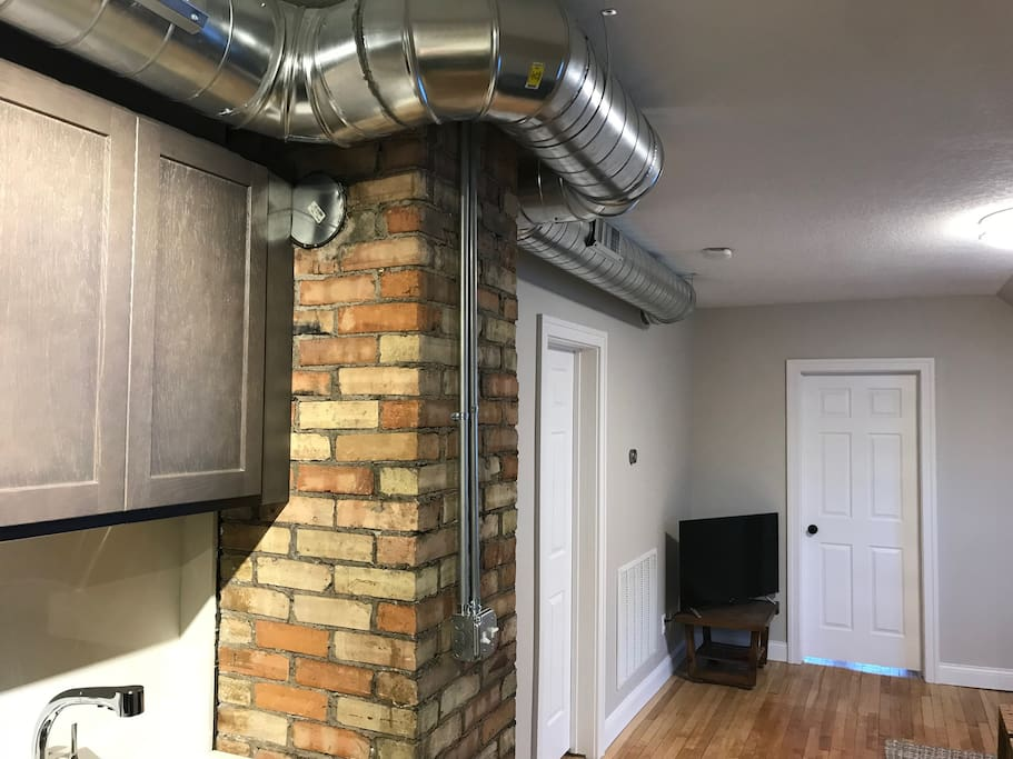 Industrial loft style apartment with exposed ductwork, high ceilings, electrical conduit and an original 1901 brick chimney