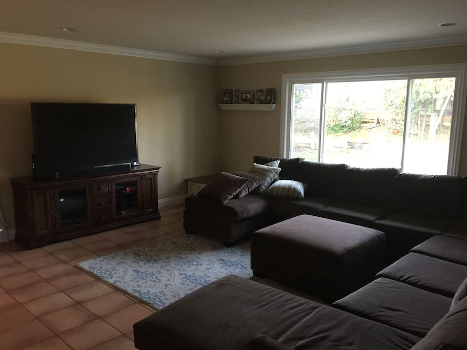 Living Room with enormous 9 person sectional and 60 inch flat screen TV (with full cable package)