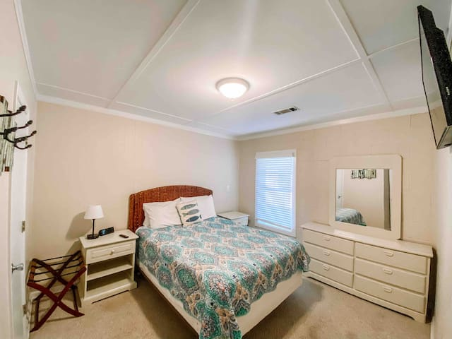 Queen guest room with wall mounted tv