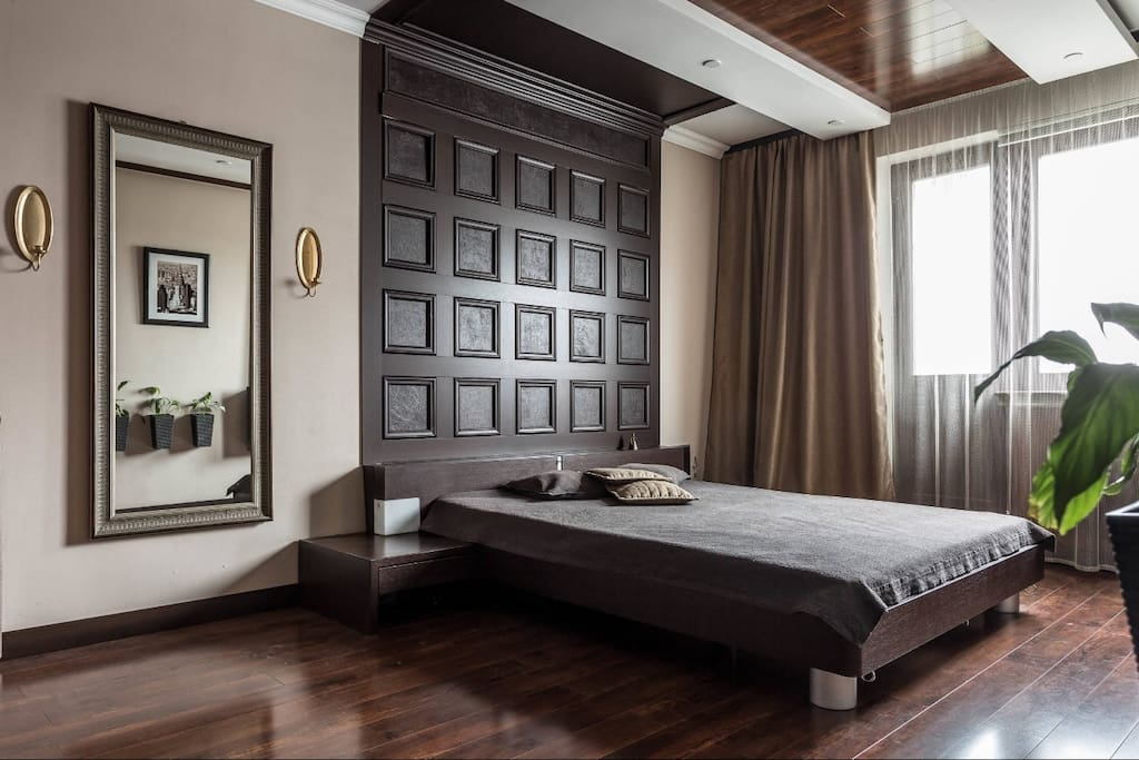 Bedroom, view from the entrance: 6.5 foot bed with chocolate headboard and large mirror. Спальня, вид со входа: двухметровая кровать с шоколадным изголовьем и большое зеркало.