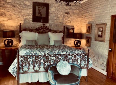 Spacious separate master bedroom with vaulted ceiling, mesquite wood floors, original art, King bed with lux linens.