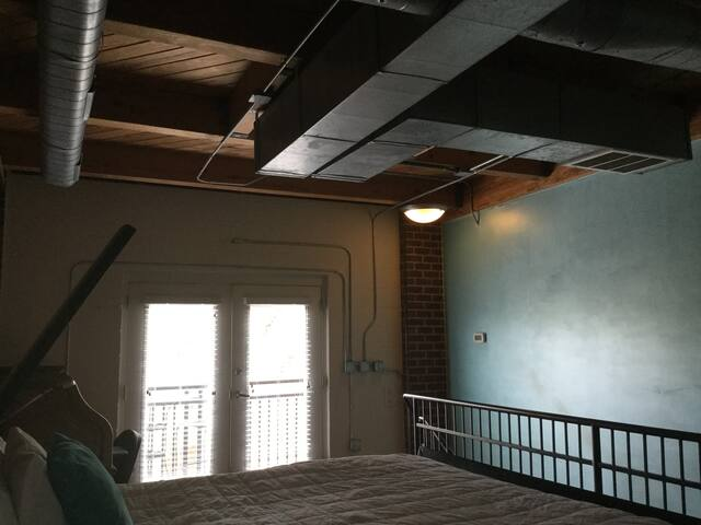 Upstairs with cozy balcony and exposed ductwork over the bed.