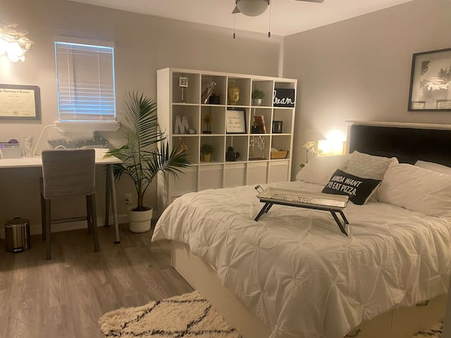 Large bedroom with a queen bed and dedicated work space also.