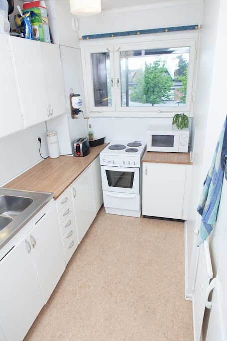Kitchen with microwave, oven, fridge and freezer.