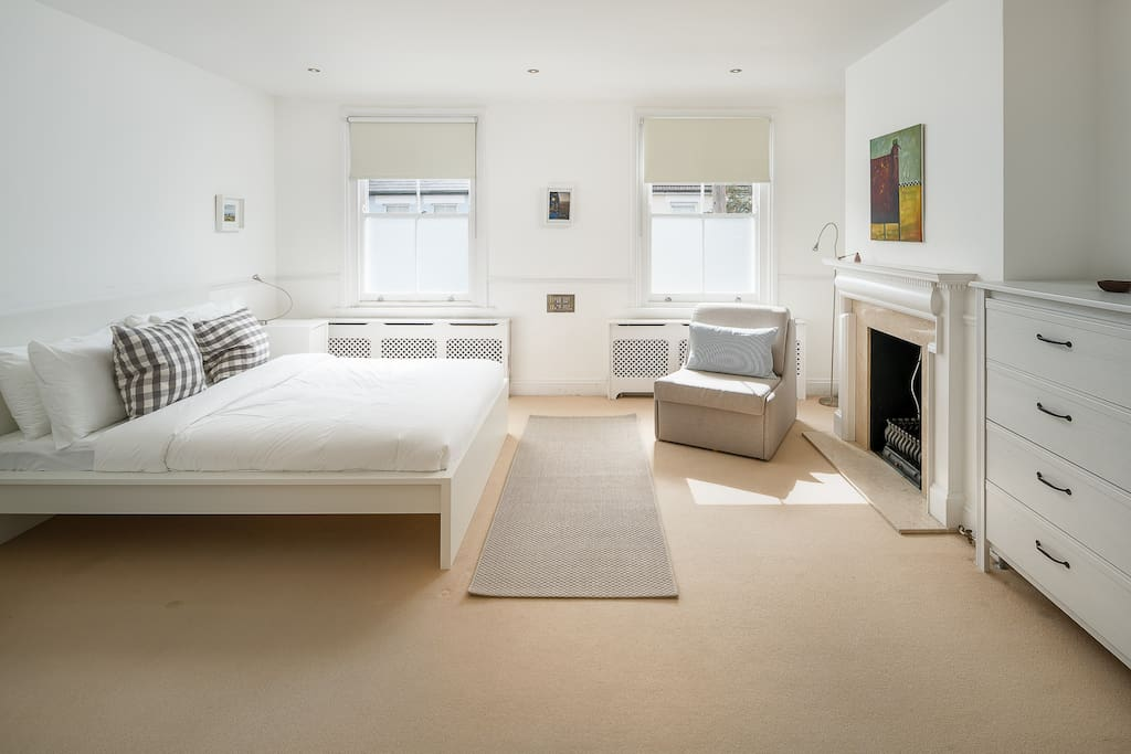 The bedroom features a fireplace and two windows allowing pleanty of natural light in