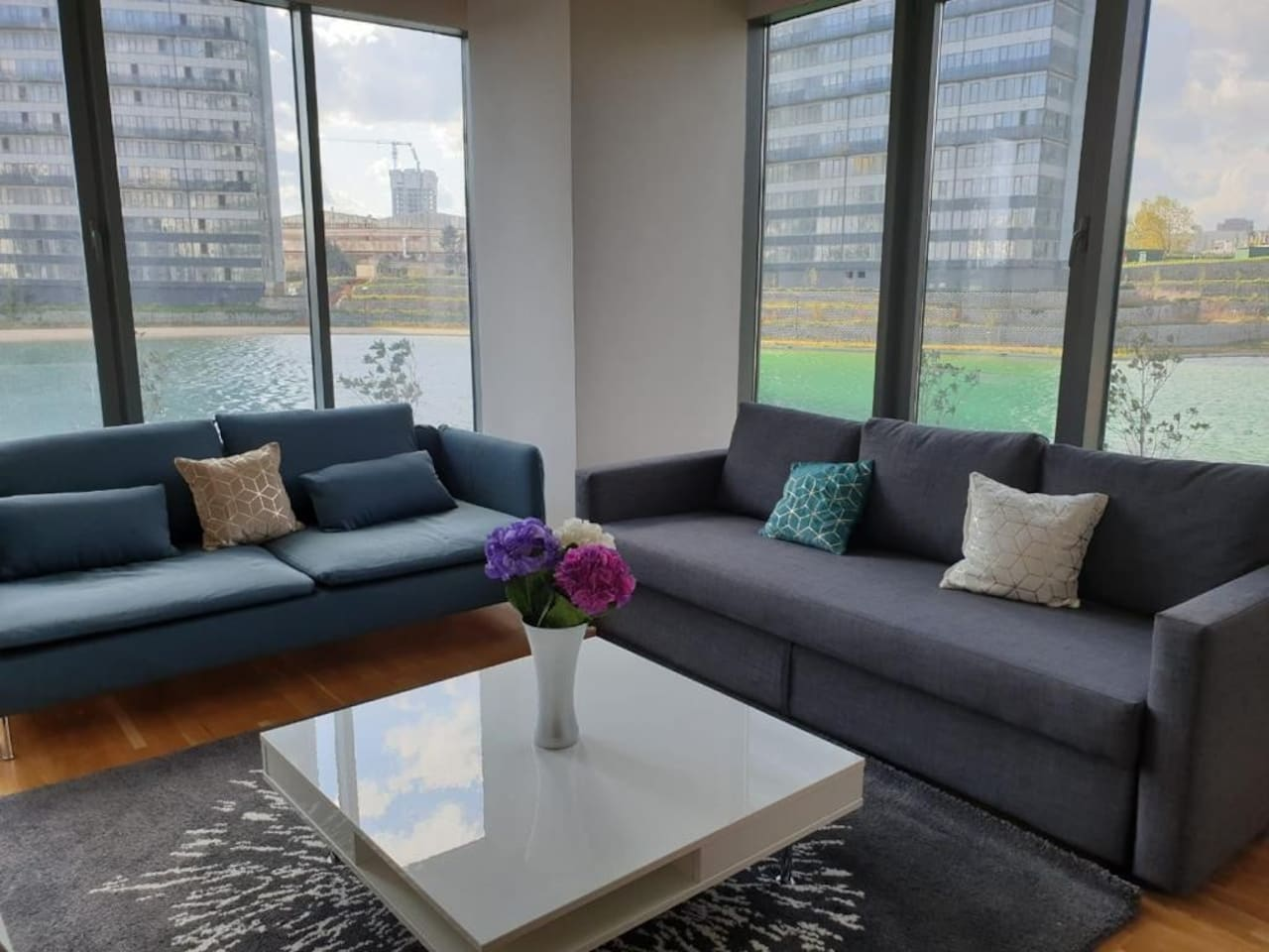 The living room doubles as a dining room with a table suitable for 6 against the far wall. It has views of the lake from all sides and a Smart TV to watch Netflix on. The grey couch doubles as a bed and can be pulled out at night