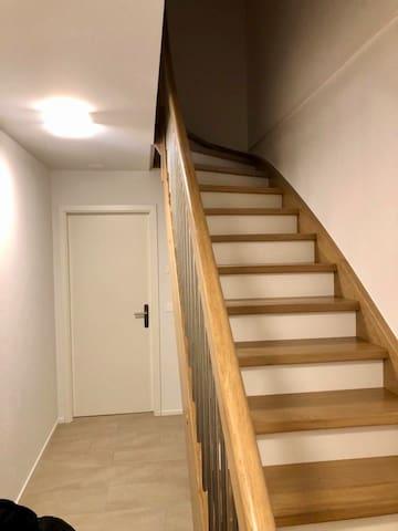 Treppe vom Vorraum. Danach kommt das Gästezimmer. Vorraum mit eingebautem Kleiderschrank, kleiner Stauraum unter der Treppe.