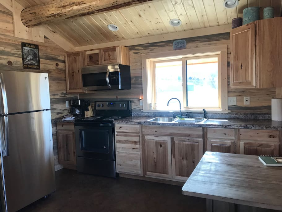 The full kitchen features a range, microwave oven hood, large refrigerator with top freezer, deep stainless double sink, hickory cabinets, coffee maker and furnished kitchen utensils and cookware.