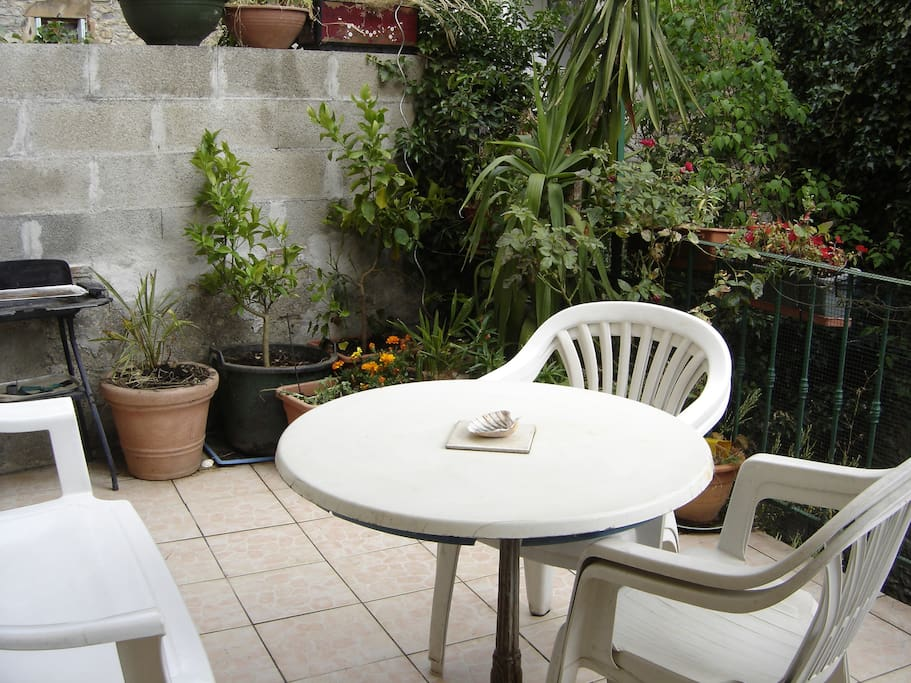 Terrasse : salon de jardin, grand parasol et barbecue...