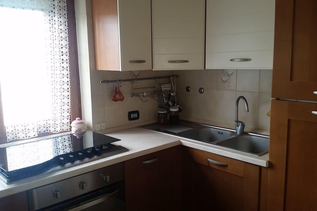 Cucina con lavastoviglie, frigo e utensili vari