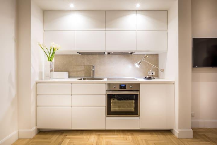 Cucina moderna completamente attrezzata con lavabo, frigo, lavastoviglie, piano cottura ad induzione, forno elettrico, macchina caffè Nespresso.