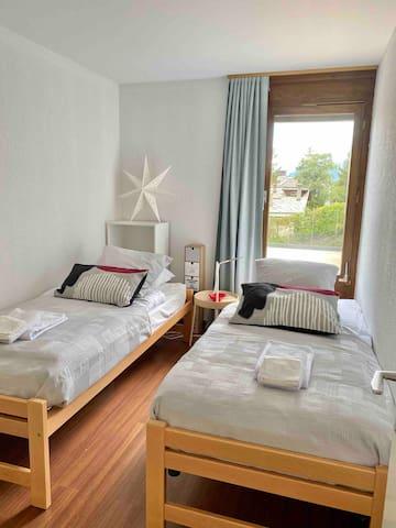 Chambre 2, avec 2 lits gigognes (90x200), 1 fenêtre vue tennis, bois et montagne. 1 armoire de rangement, table d'appoint, meuble étagères. Planche à repasser. Fermée par une porte.