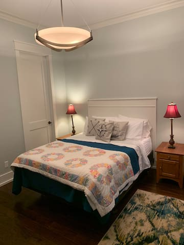 Your bedroom with queen size bed, bedside tables, and lamps.